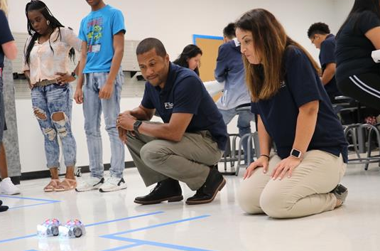 Superintendent Dr. Johnson (left) watches robot with Assistant Superintendent Keira Scussa.
